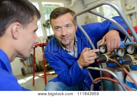 Man with trainee pointing to gauge