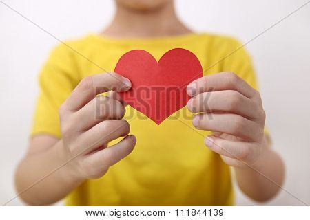 red heart on hand little boy