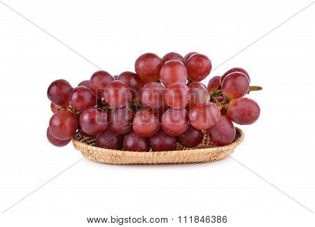 Bunch Of Red Grape In Rattan Basket On White Background