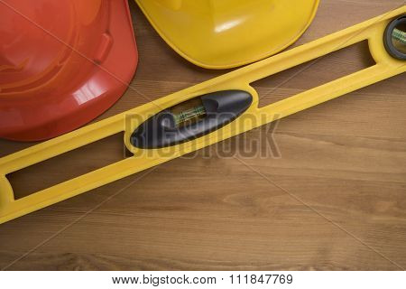 Yellow Building Level And Helmets On The Old Wood Table