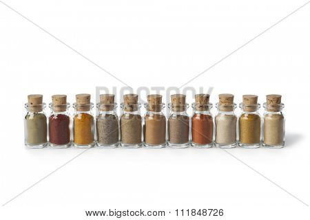 Row of glass bottles with different powder herbs on white background