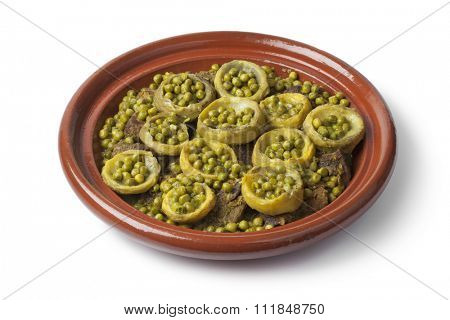 Traditional Moroccan tagine with meat, artichoke hearts and green peas on white background