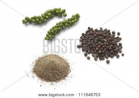 Fresh green pepper drupes, black pepper and powder on white background