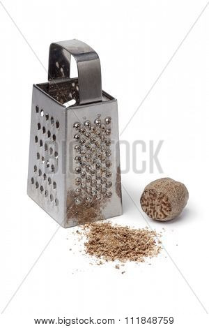Ground nutmeg kernel and grater on white background