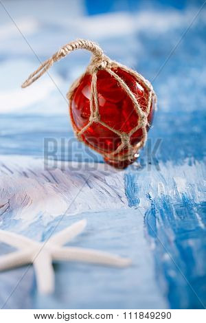 red Glass float with white starfish  on blue painted background