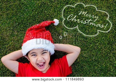 Little Asian girl in santa hat on the green grass with text