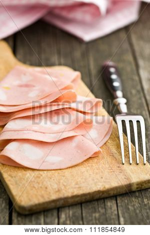Slices of Sausage Mortadella and fork on cutting board