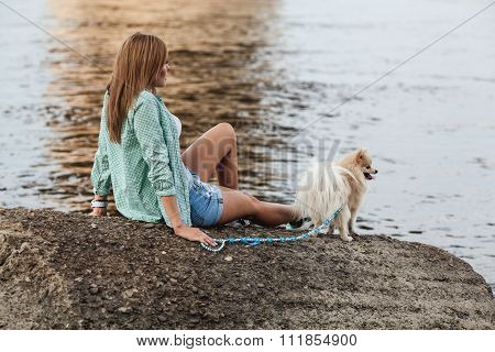 Young adult  woman and her dog sitting on rocks