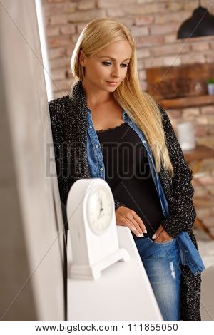 Thoughtful young woman standing against wall at home.