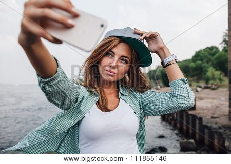 beautiful young adult woman taking picture of herself, selfie. She hold cap on her head
