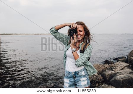 beautiful girl takes photographs with vintage photo camera outdoor