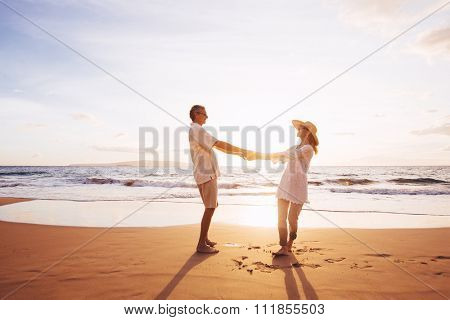 Happy Romantic Middle Aged Couple Enjoying Beautiful Sunset on the Beach. Travel Vacation Retirement Lifestyle Concept.