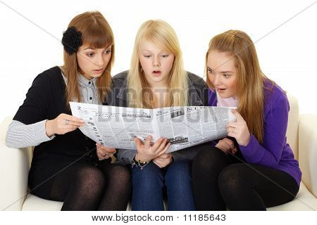 Three Young Girls Reading Newspaper