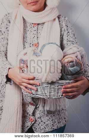 Woman with basket of balls woolen yarn