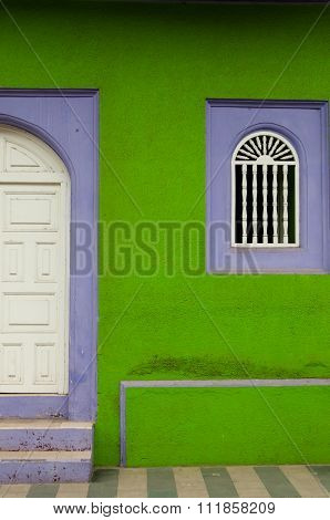 Green and purple stone wall of colonial house with white wooden closed door in Granada