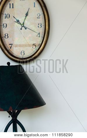Old watch hanging on wall with lamp and lampshade