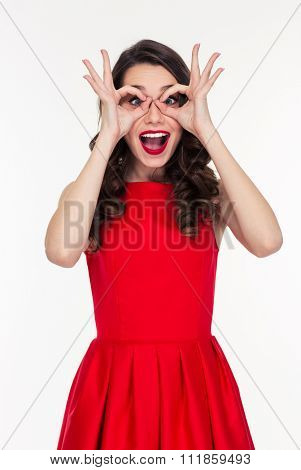 Portrait of a cheerful woman looking at camera through fingers isolated on a white background