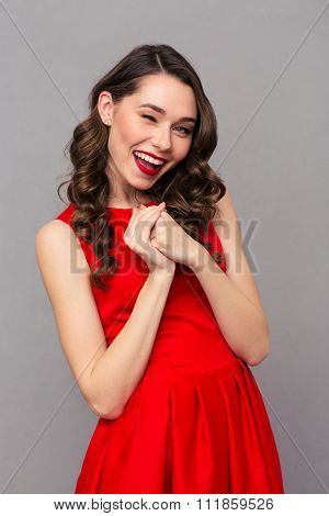 Portrait of a pretty woman in red dress winking at camera over gray background