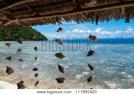 Shells Hanging From Bamboo Roof in front of crystal clear water and white sand beach