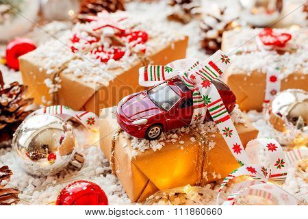 Christmas And New Year Background With Toy Car Present With Ribbon. Balls, Pinecones And Different D