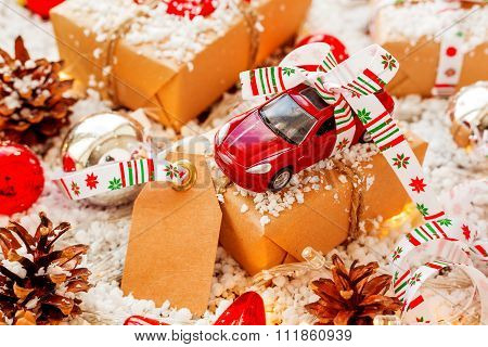 Christmas And New Year Background With Toy Car Present With Ribbon And Clear Tag. Balls, Pinecones.