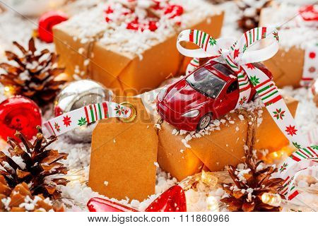 Christmas And New Year Background With Toy Car Present With Ribbon And Clear Tag. Balls, Pinecones A