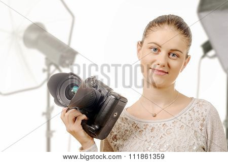 Portrait Of Beautiful Photographer Smiling With Digital Camera In Studio