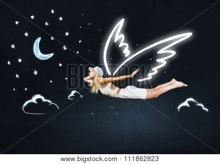 Cute girl with angel drawn wings on dark sky background