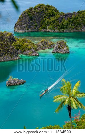Boat Cruising Around small green Islands belonging to Fam Island in the sea of Raja Ampat, Papua New