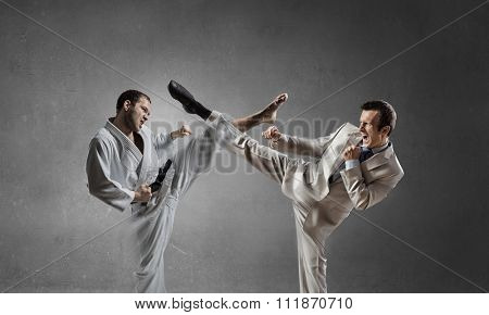 Young determined karate man fighting with businessman in suit