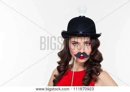 Close up of funny serious young curly woman in ridiculous black hat with light bulb posing using paper moustache booth