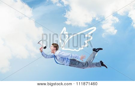 Young businessman with wings flying in sky and talking in megaphone