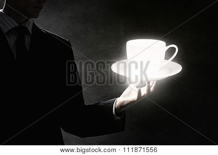 Close up of businessman hand holding white cup