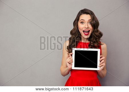 Portrait of a cheerful woman in red dress showig blank tablet computer screen over gray background