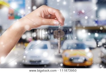Keys in hand on blurred cars background over snow effect