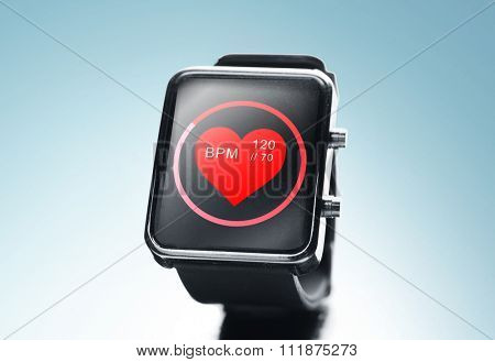 modern technology, object, health care and media concept - close up of black smart watch showing red heart beat icon on screen