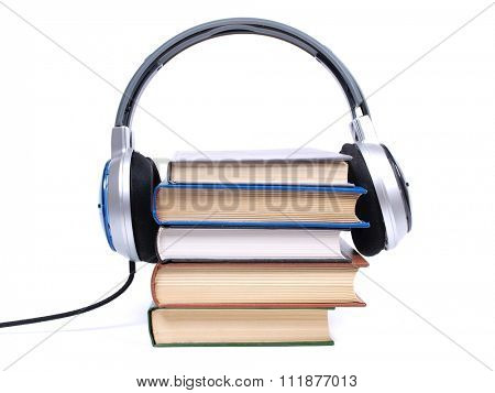 Stack of books and headphones on white background