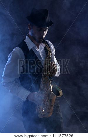 Elegant saxophonist plays jazz on dark background in blue smoke