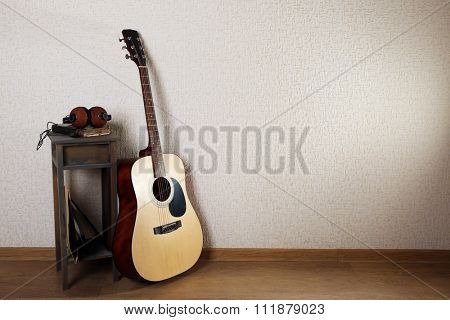 Acoustic guitar propped on wall with stool and headphones on it in the room