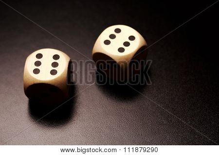 Two wooden dices on a black background.
