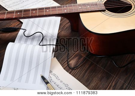 Guitar and music sheets on wooden background