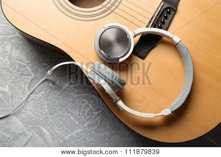 Classical guitar and headphones on grey background