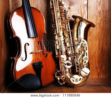 Close up view on musical instruments: saxophone, violin in wooden box