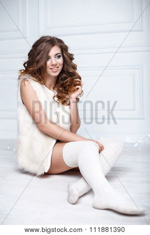 Young Stylish Woman In Warm Clothes And Knitted Socks Sitting On The Floor Against A Light Backgroun