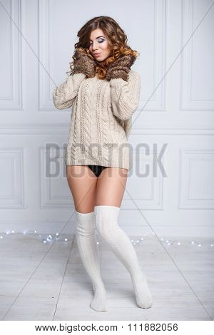 Young Beautiful Woman In Winter Warm Clothes And White Stockings On The Background Of Lights