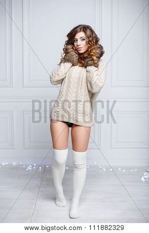 Young Sexy Girl In Warm Clothes And Knitted Mittens Standing Near The Wall Of The Room