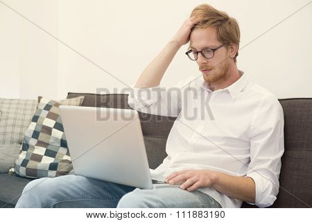 Young Man Sitting On Couch With Laptop