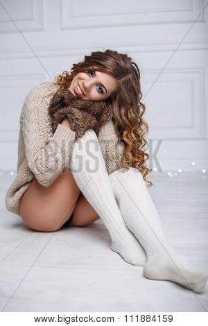 Pretty Woman In Winter Mittens Sitting On The Floor
