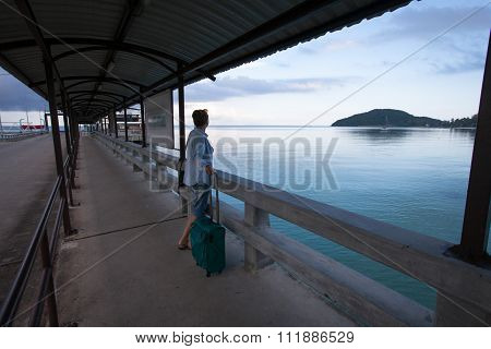 Woman Standing With A Suitcase Waiting For The Ferry.