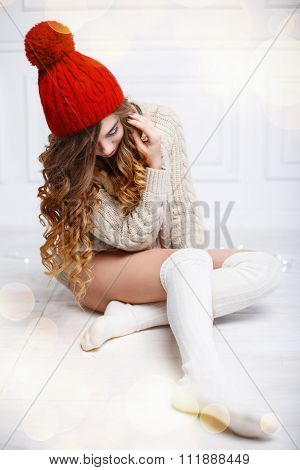 Beautiful Fashionable American Girl In Knitted Warm Clothes On A Background Of Lights. Woman Sitting
